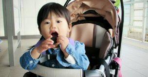 ベビーカーでおにぎりを食べる子ども